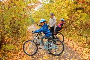 Happy family on bikes in autumn park, having fun